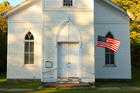 White country church and U.S. flag (iStock)