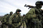 The Russians are coming? Armed men, believed to be Russian servicemen, march outside a Ukrainian military base in Crimea on March 7.