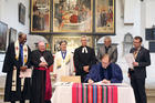 Reformed, Catholic, Lutheran and Methodist leaders look on in St. Mary's City Church in Wittenberg, Germany, as the Rev. Chris Ferguson, World Communion of Reformed Churches general secretary, signs the declaration expressing Reformed churches' support for the Catholic-Lutheran Joint Declaration on the Doctrine of Justification. Photo courtesy of WCRC/Anna Siggelkow