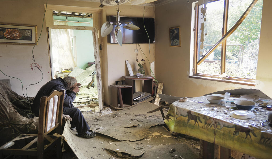 Yury Melkonyan, 64, sits in his house, damaged by shelling from Azerbaijan's artillery during a military conflict in Shosh village outside Stepanakert, the separatist region of Nagorno-Karabakh, Saturday, Oct. 17, 2020. (AP Photo)