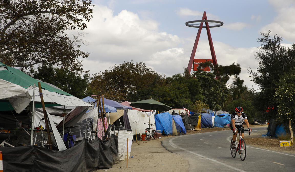 A cyclist passes the row of tents and tarps along the Santa Ana riverbed near Angel Stadium on Sept. 14 in Anaheim, Calif. Amid an uproar from residents, the city of Anaheim declared an emergency in an attempt to cope with a ballooning homeless encampment along a popular riverbed trail and speed the addition of shelter beds. (AP Photo/Jae C. Hong)