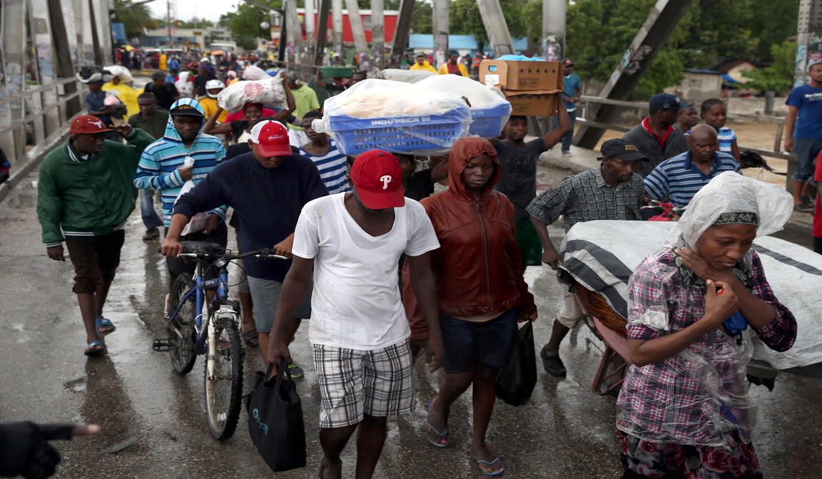 People cross a bridge over a rushing river as part of evacuations during Hurricane Matthew Oct. 4, 2016 in Port-au-Prince, Haiti (CNS photo/Orlando Barria, EPA).
