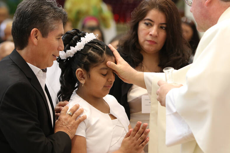 Erika Gallegos, 9, is confirmed by Father Christopher Nowak during a Mass at St. John of God Church in Central Islip, N.Y., April 11. (CNS photo/Gregory A. Shemitz)