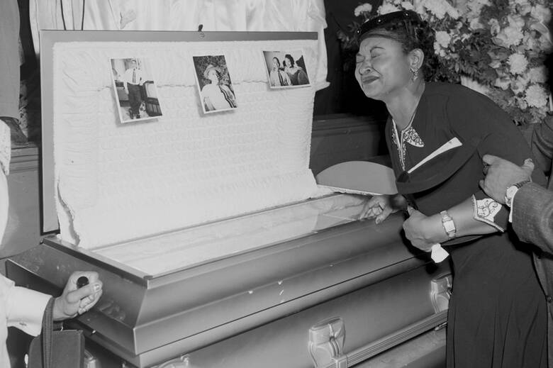 In this 1955 file photo, Mamie Bradley, mother of Emmett Till, pauses at her son's casket at a Chicago funeral home.